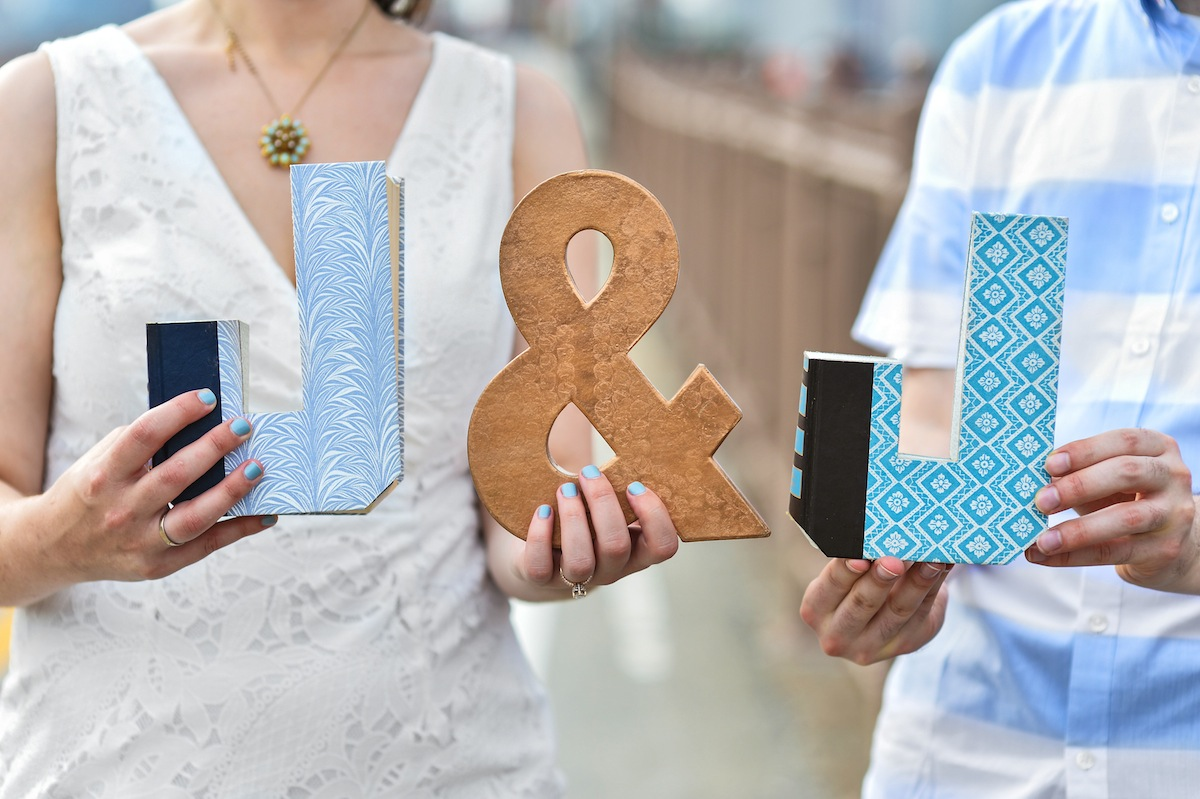 engaged-couple-holding-initial-signs-ny-photography