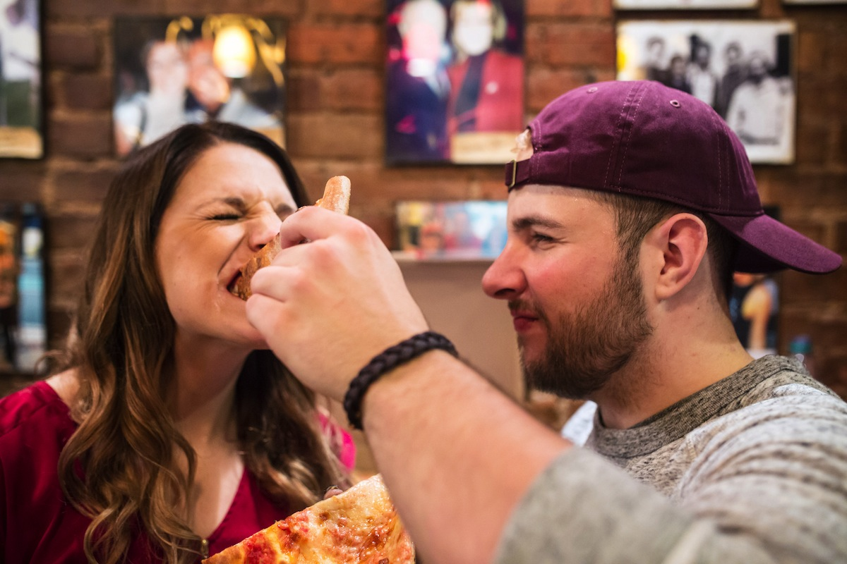 alex-giving-laura-bite-of-pizza-engagement-photography-ny