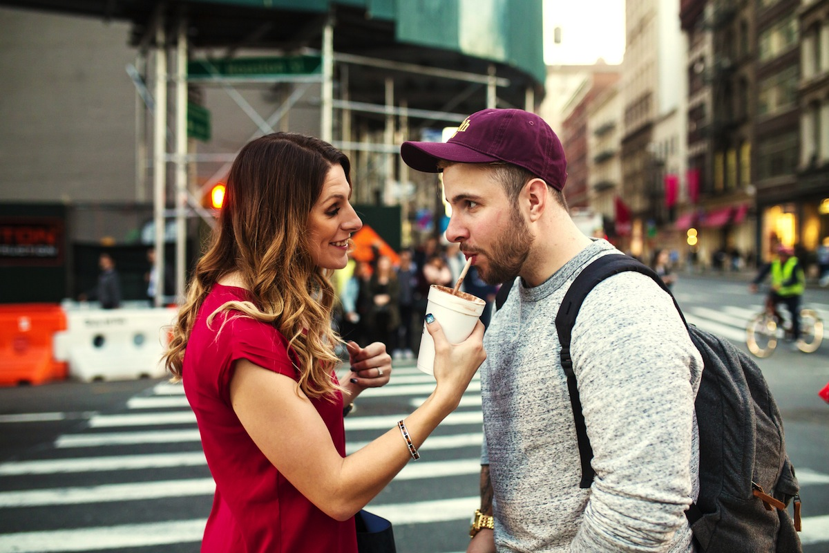 alex-sipping-lauras-drink-on-street-nyc-engagement-photography