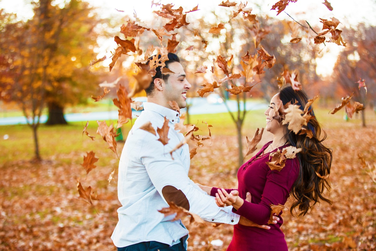 jason-and-stephani-laughing-as-leaves-float-around-them-in-park-nj-engagement-photos