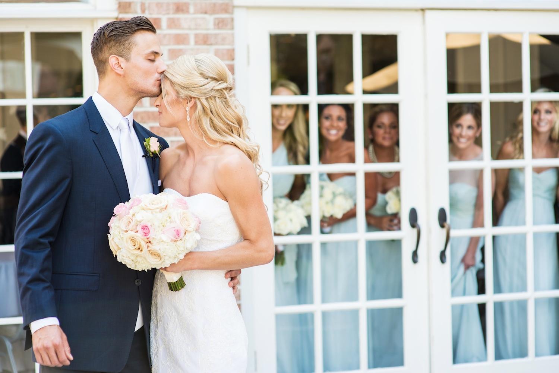brandon-kissing-alicia-as-bridesmaids-watch-through-window-nj-wedding-photos