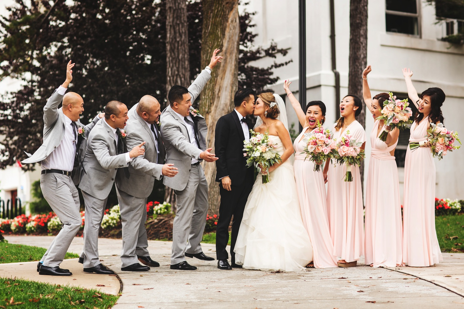 evan-and-gracie-kissing-outside-surrounded-by-cheering-wedding-party-nj-photography