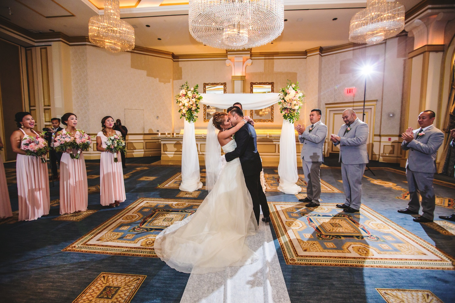 gracie-and-evan-kissing-at-altar-while-wedding-party-claps-nj-photography