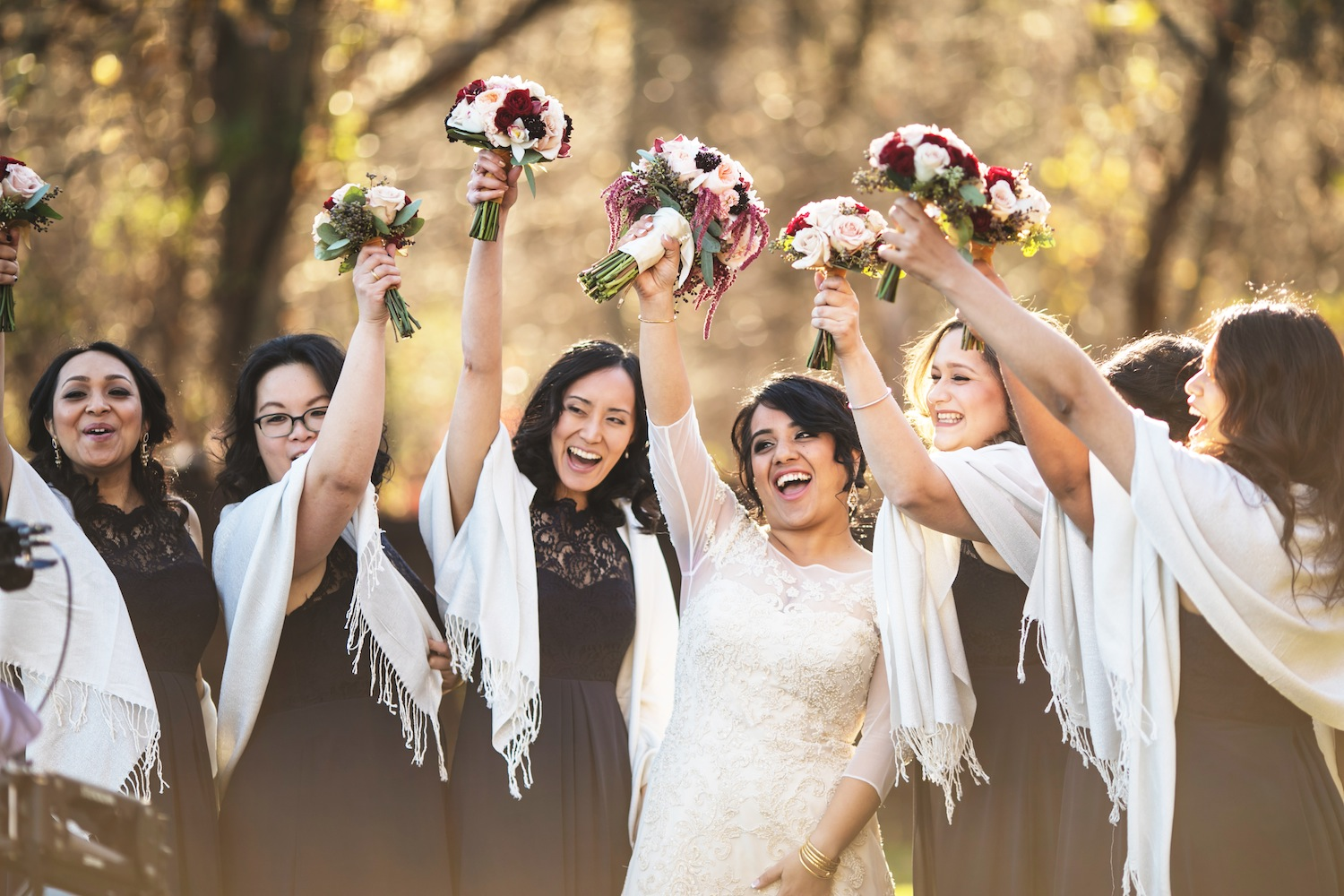 kamana-and-bridesmaids-raising-bouquets-in-air-in-celebration-nj-wedding-photography