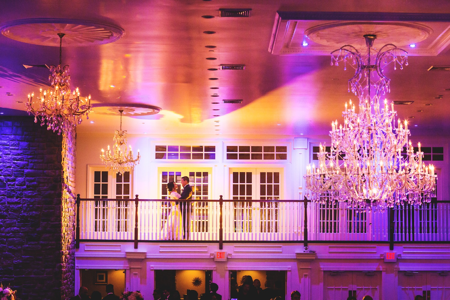 rob-and-kamana-embracing-on-balcony-in-colorful-venue-wedding-photography-nj