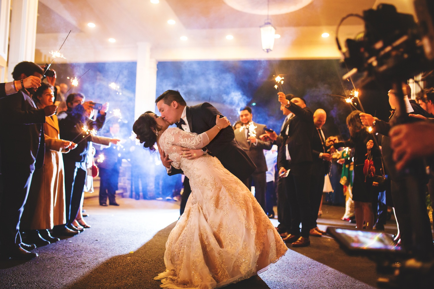 rob-dipping-and-kissing-kamana-as-guests-cheer-with-sparklers-nj-wedding-photography