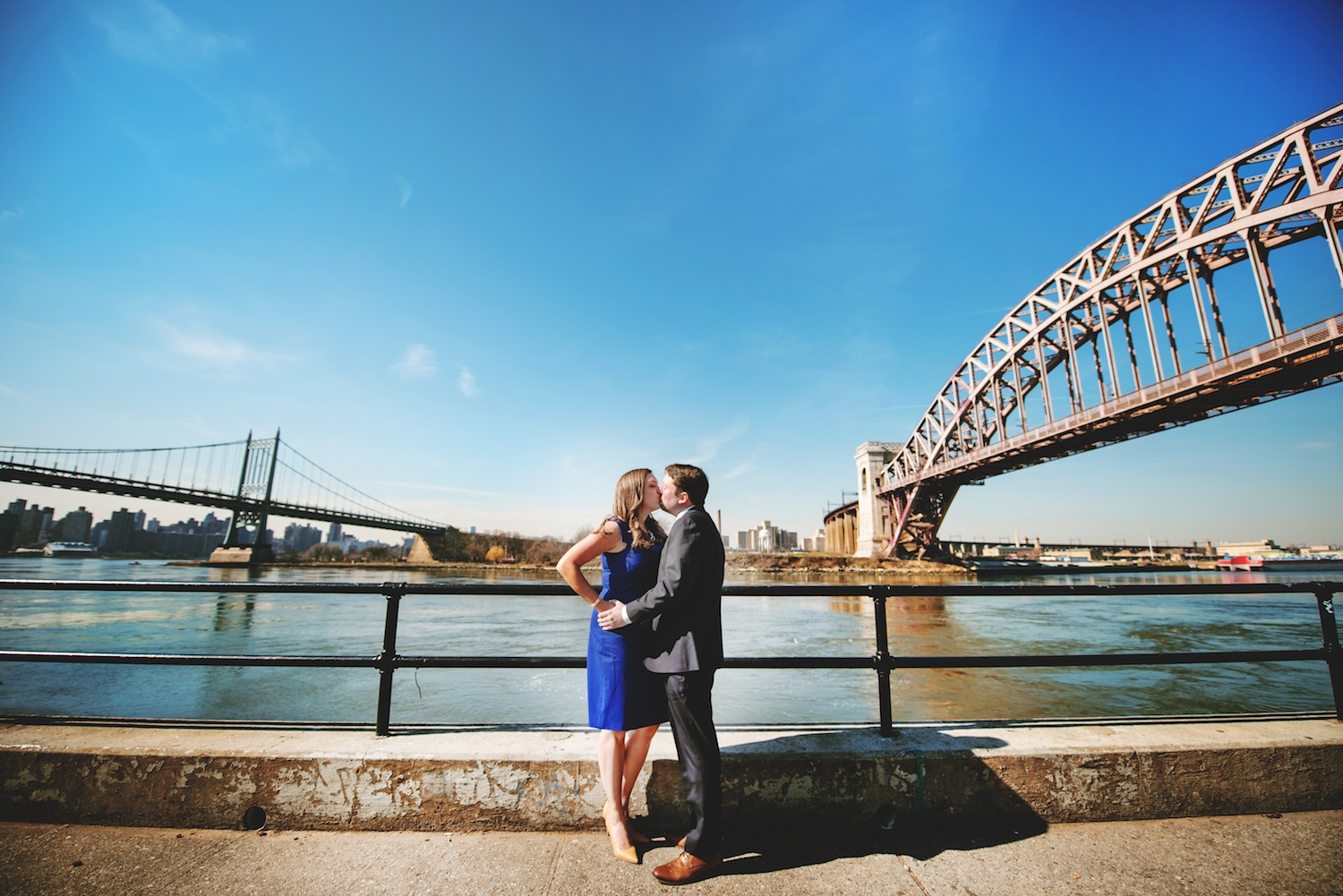alison-and-brian-kissing-by-water-between-bridges-nyc-engagement-photos