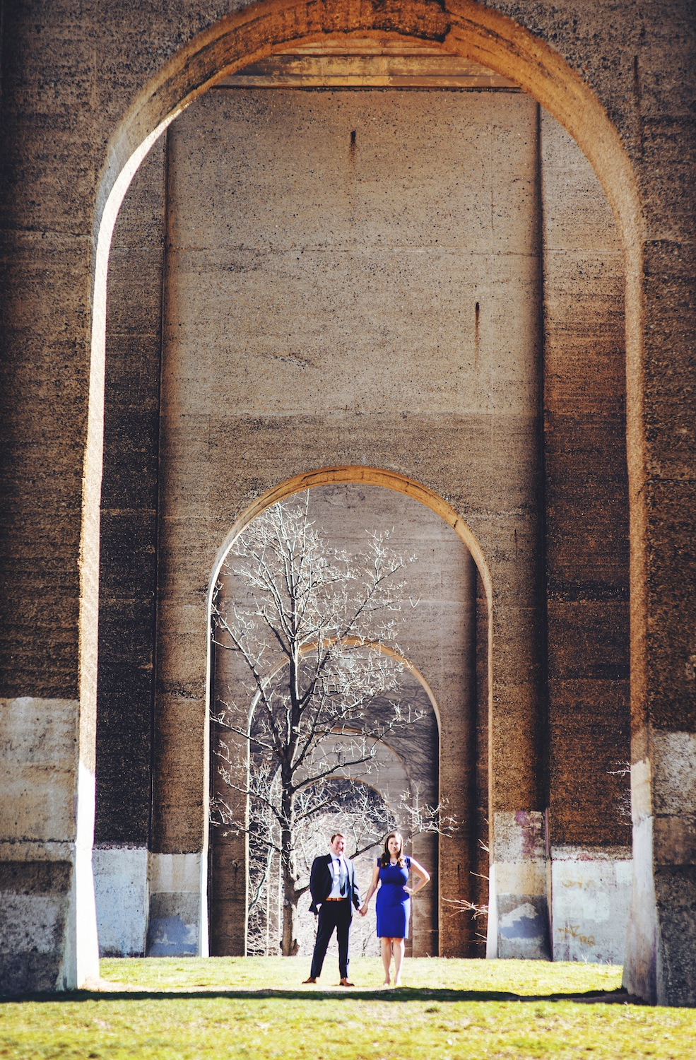 brian-and-alison-standing-under-archways-in-engagement-photography-nyc