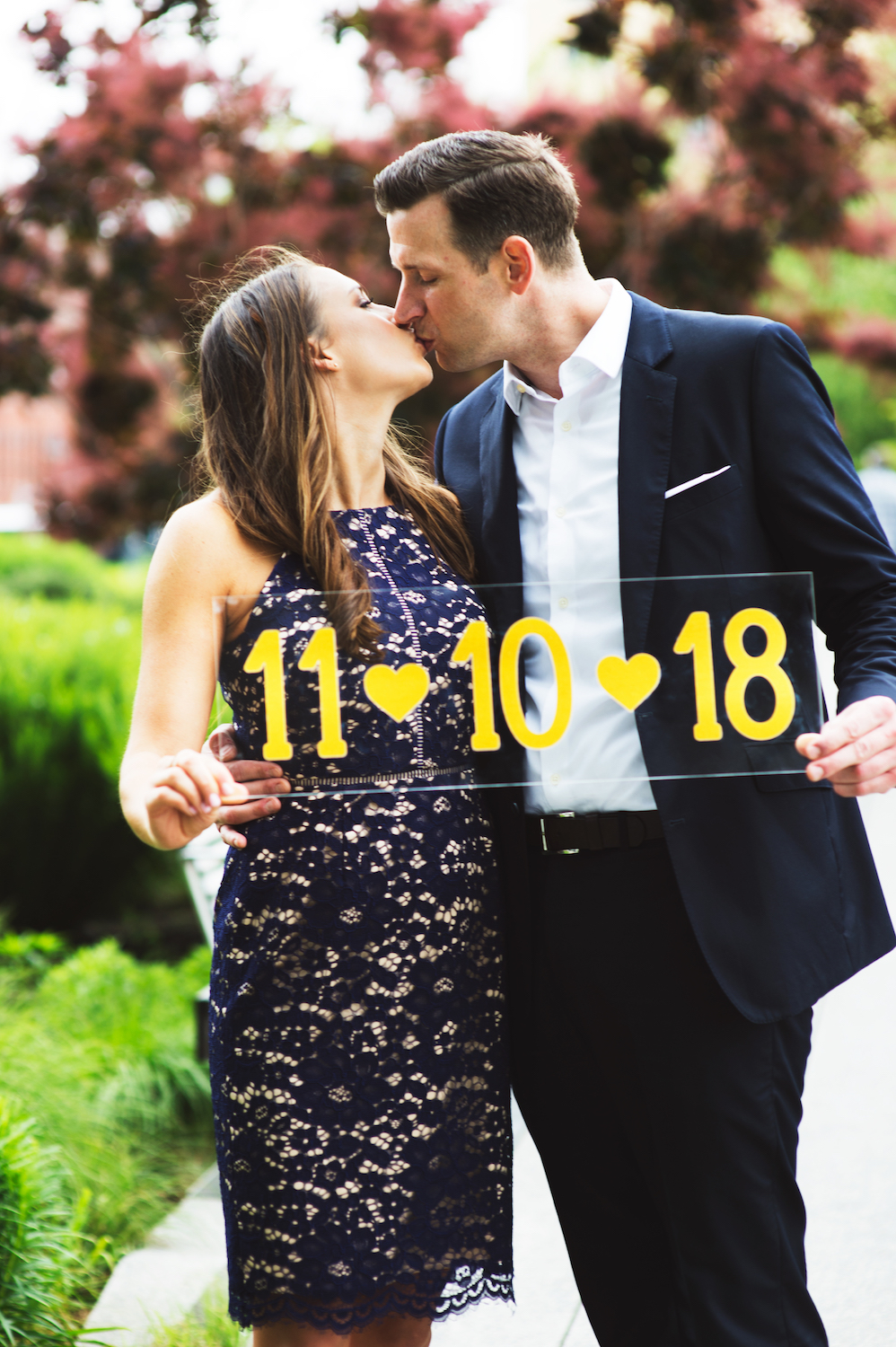 kayla-&-mike-kissing-while-holding-wedding-date-sign-nyc-nj-engagement-photos