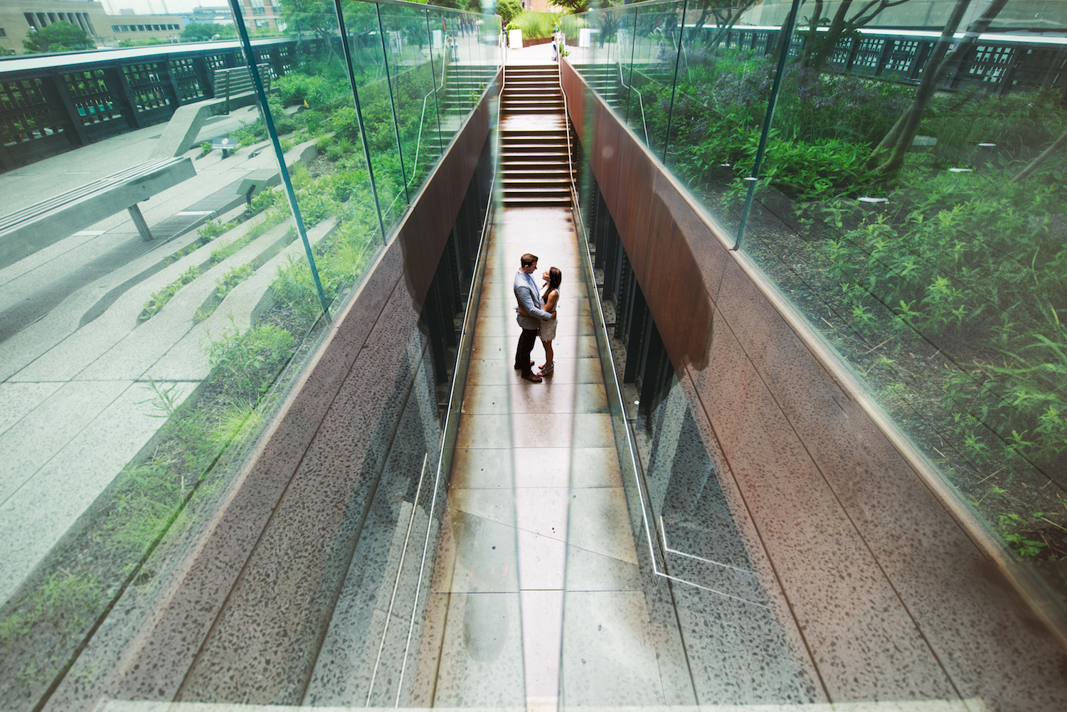 mike-&-kayla-embracing-in-glass-walled-walkway-ny-nj-engagement-photos