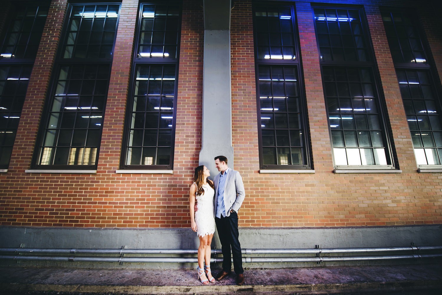 kayla&mike-standing-by-brick-wall-nyc-engagement-photography
