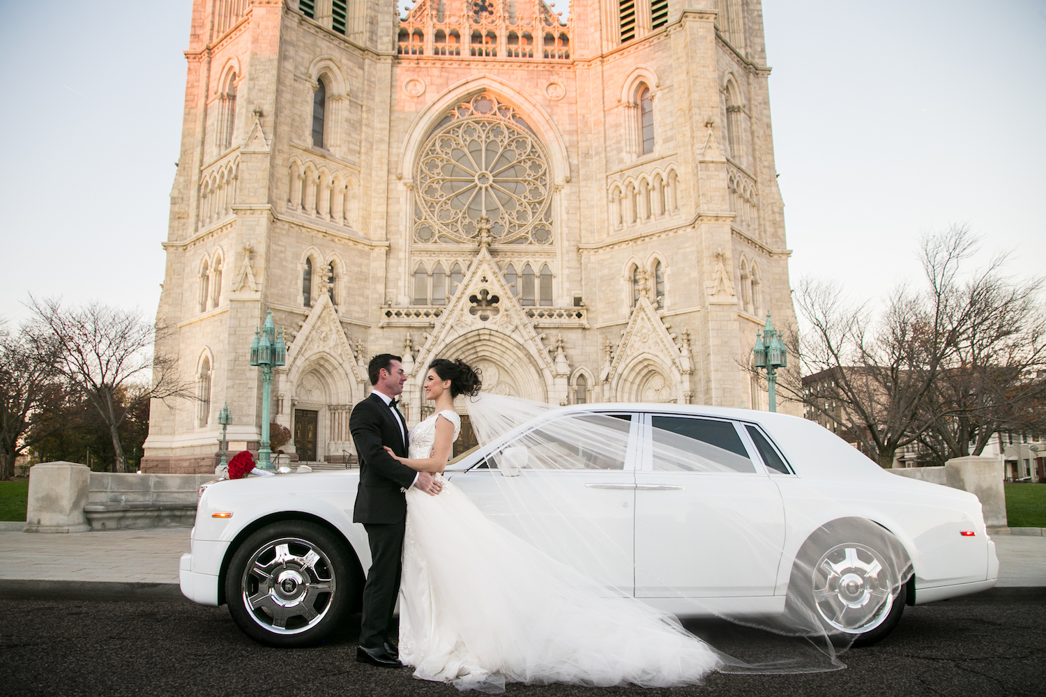 christian&jessica-embracing-by-classic-car-outside-church-nj-wedding-photography