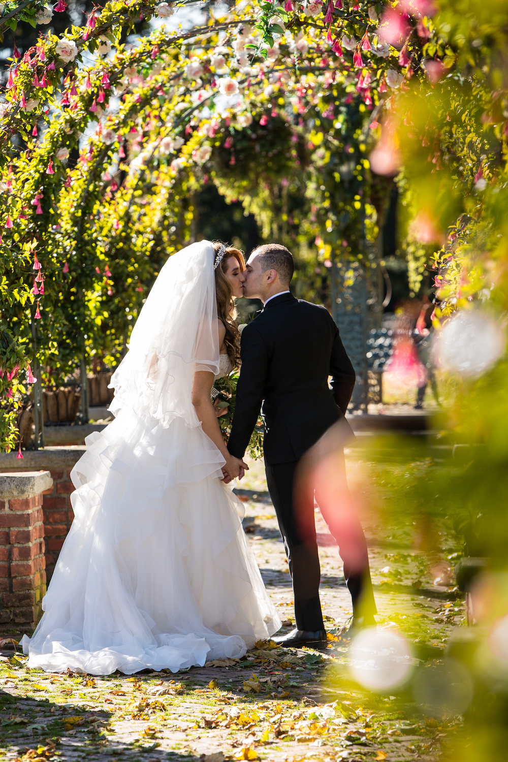 nada&amro-kissing-in-garden-archway-outside-wedding-photography-nj