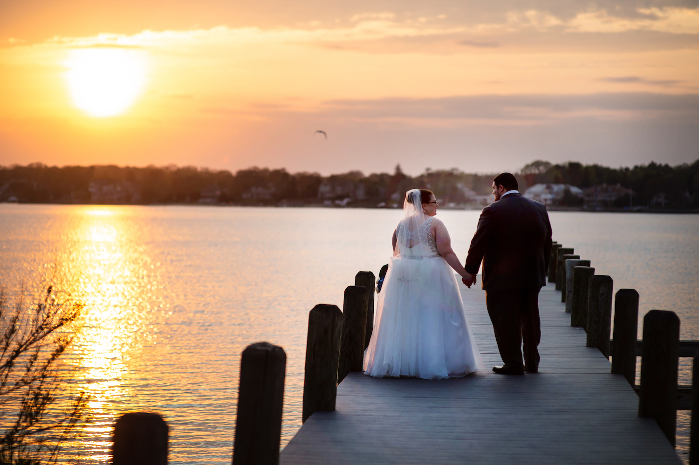 nj-wedding-photographers-alli&mickey-walking-holding-hands-dock-dusk