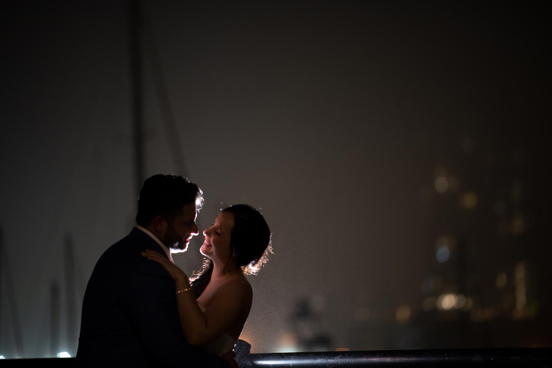 nj-wedding-photographers-denise&jason-embracing-smiling-by-boats